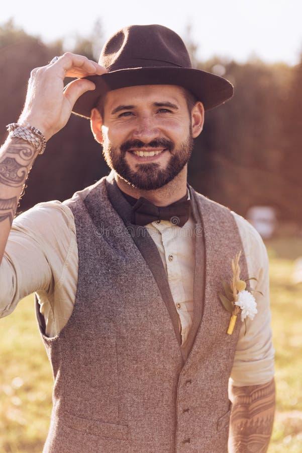 时髦的胡子,与纹身花刺的男性画象在他的胳膊 背景新娘花卉新郎装饰品纵向婚礼 库存照片