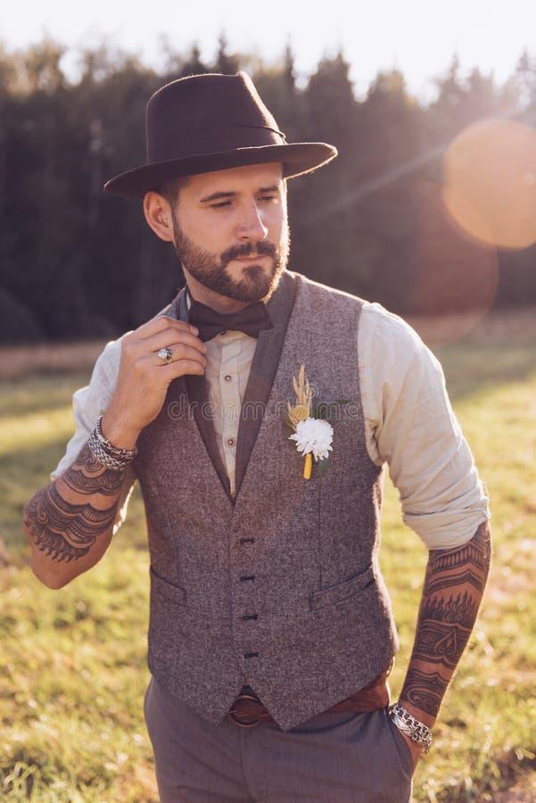 时髦的胡子,与纹身花刺的男性画象在他的胳膊 背景新娘花卉新郎装饰品纵向婚礼 免版税库存照片