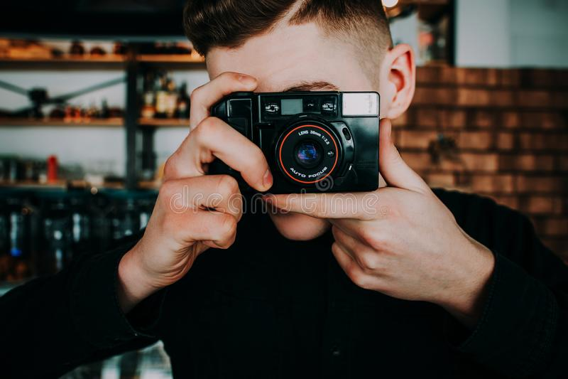 时髦的英俊的人画象有照相机的 库存图片