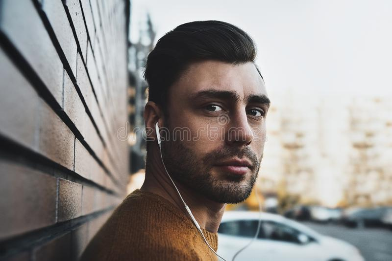 时髦的英俊的年轻人画象有站立的刺毛的户外 图库摄影