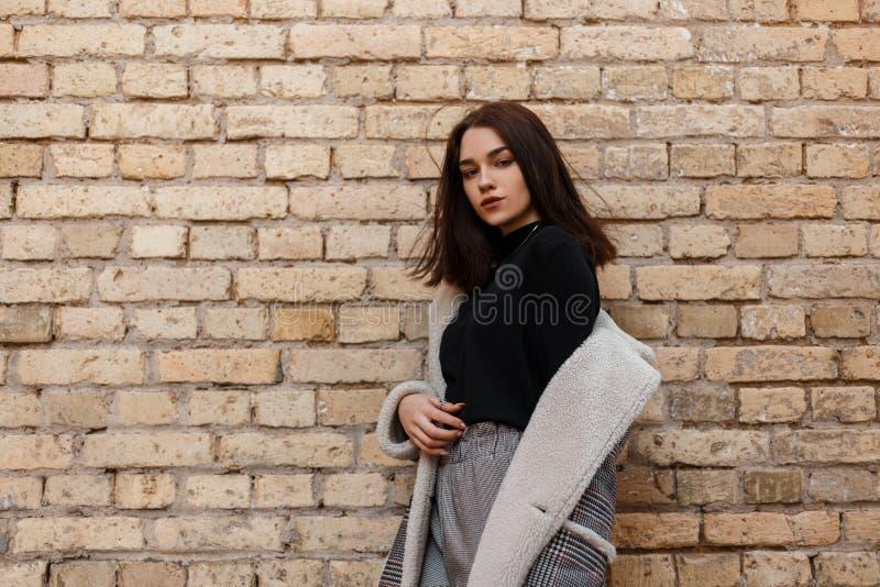 时髦的葡萄酒衣裳的俏丽的现代年轻女人在摆在户外在城市的减速火箭的样式在砖墙附近 库存照片