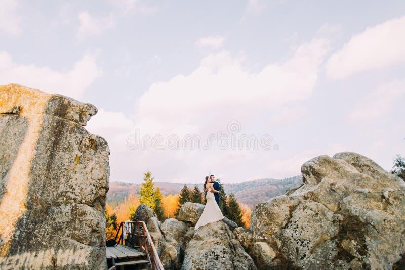 时髦的蓝色衣服的英俊新郎接受白色的打扮了田园诗室外风景的新娘与大岩石和多云 免版税库存图片