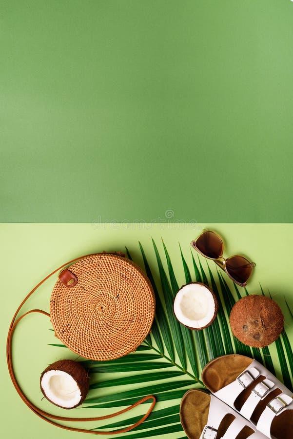 时髦的藤条袋子,椰子, birkenstocks,棕榈分支,在橄榄绿背景的太阳镜 钞票 顶视图与 图库摄影