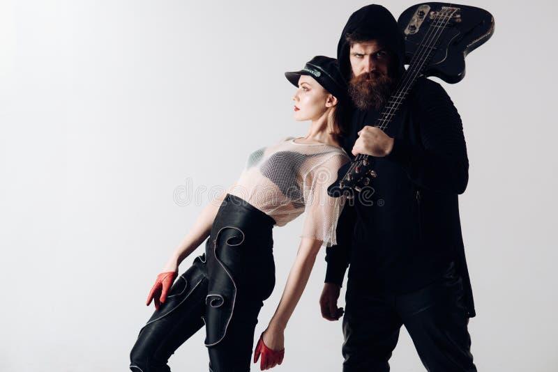 时髦的行家和妇女与电吉他一起 晃动性感的女孩和有胡子的人夫妇有吉他的 凉快的岩石 免版税图库摄影