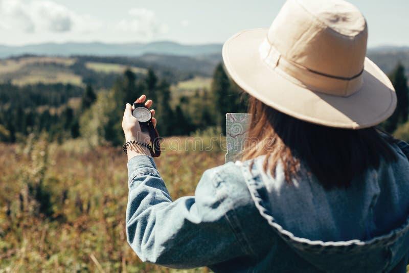 时髦的行家女孩藏品地图和指南针,旅行在晴朗的山 帽子探索的地图的妇女和远足在顶部 免版税库存图片