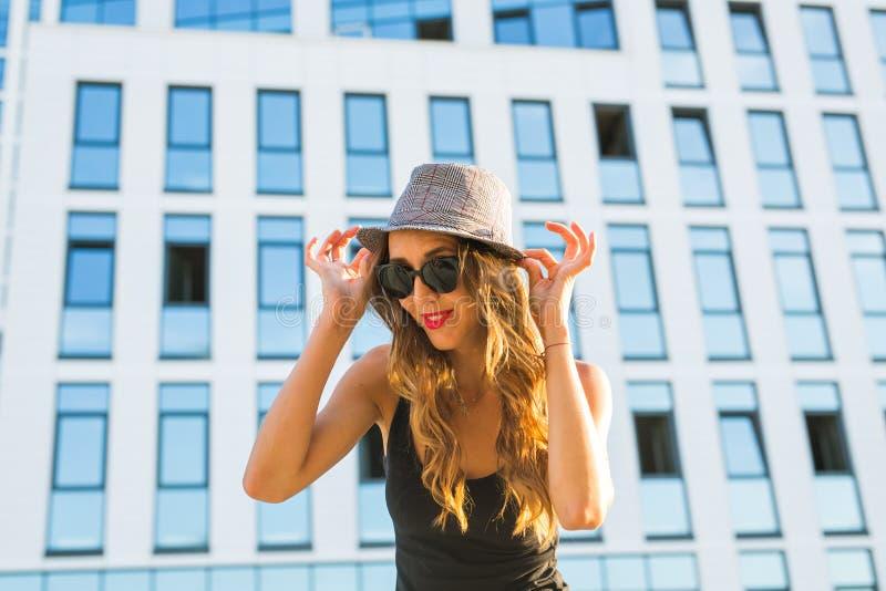 年轻时髦的行家妇女走在街道上的,佩带的时髦成套装备晴朗的生活方式特写镜头时尚画象  免版税库存图片