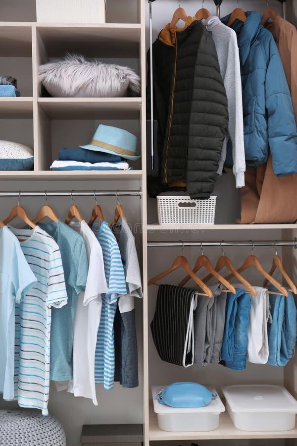 时髦的衣裳和家庭材料在大衣橱 图库摄影