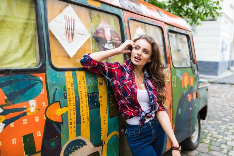 时髦的衣裳的年轻美丽的女孩在摆在城市街道的老打破的公共汽车前面 库存图片