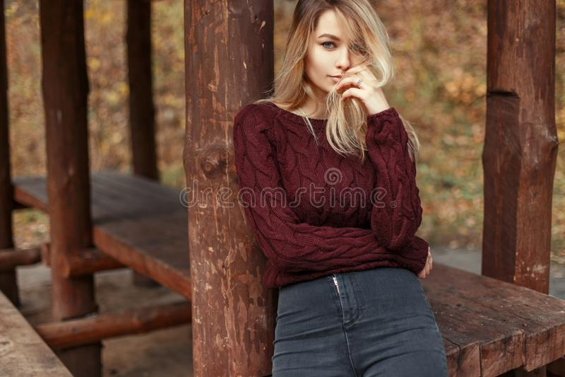 时髦的被编织的毛线衣和牛仔裤的美丽的年轻白肤金发的女孩 免版税库存图片