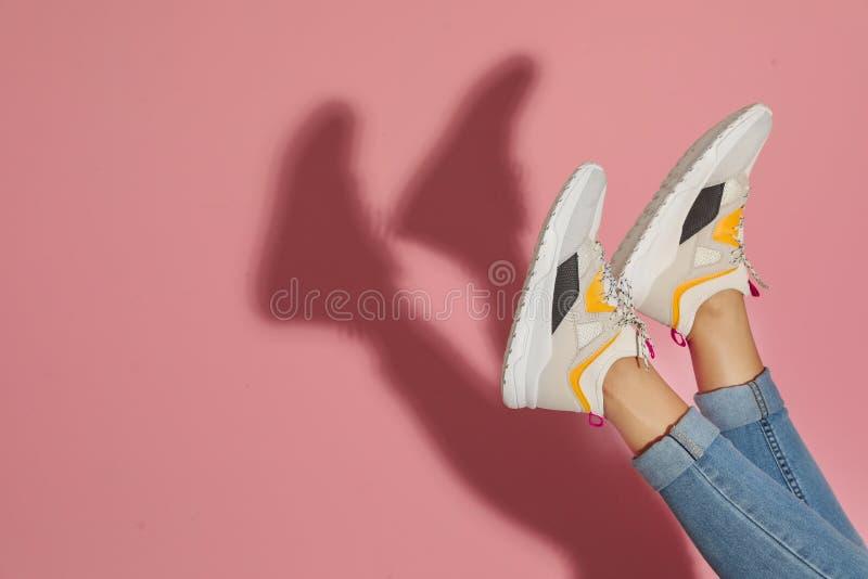 时髦的运动鞋的妇女临近颜色墙壁,特写镜头 免版税库存照片
