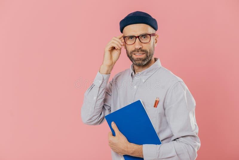 时髦的遥远的工作者戴透明眼镜,时髦的帽子,衬衣,拿着蓝色课本,写的信息用途铅笔, 库存照片