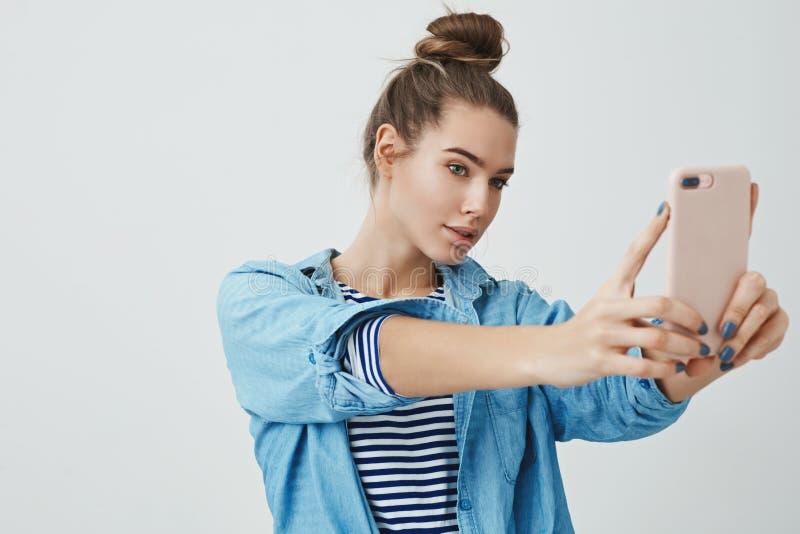 时髦的采取selfie的魅力年轻25s女性互联网博客作者夺取完美构成,摆在厚脸皮私秘看 免版税库存照片