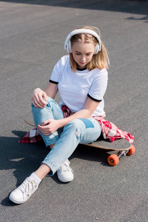 时髦的青少年的在耳机的女孩听的音乐,当坐时 库存照片