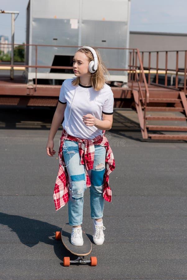 时髦的青少年的女孩骑马滑板 库存照片
