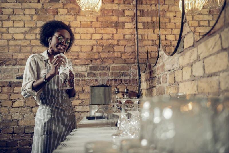 时髦的非裔美国人的在酒吧的女服务员佩带的围裙发光的酒杯 免版税图库摄影
