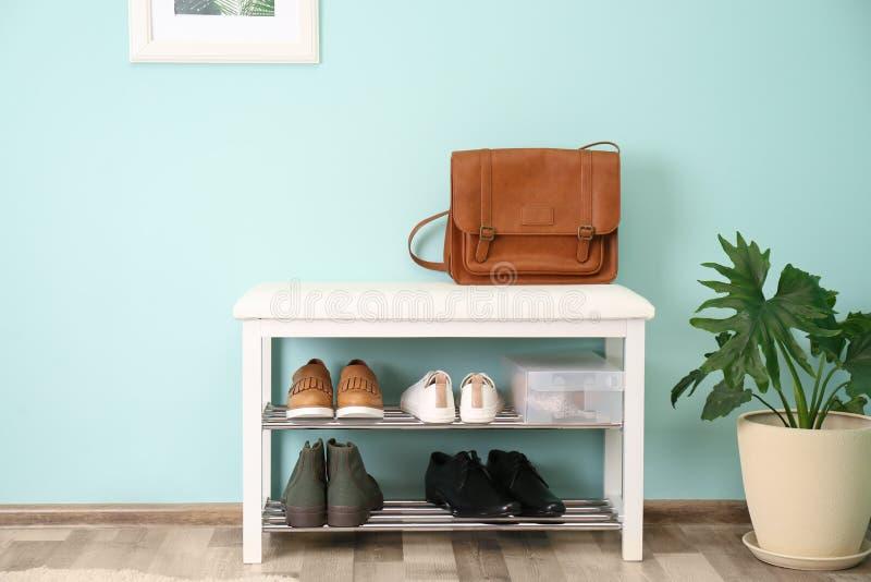 时髦的鞋子的汇集在机架存贮的在颜色墙壁附近 库存照片