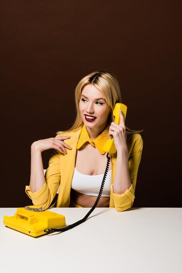 时髦的黄色衣裳的看美丽的微笑的白肤金发的女孩谈话由转台式电话和  免版税库存照片