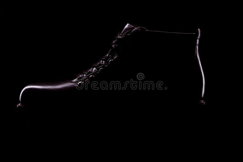 时髦的黑人鞋子剪影在黑背景的 免版税库存照片