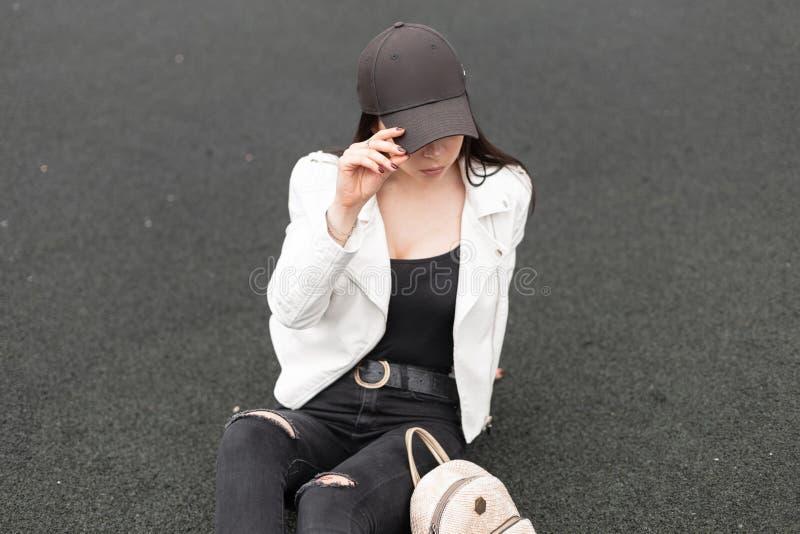 时髦的黑盖帽的俏丽的现代年轻女人在牛仔裤的一件皮革白色夹克在有金背包的一件T恤杉 图库摄影
