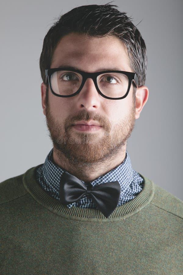 时髦的年轻人佩带的bowtie和玻璃在灰色背景。 库存图片