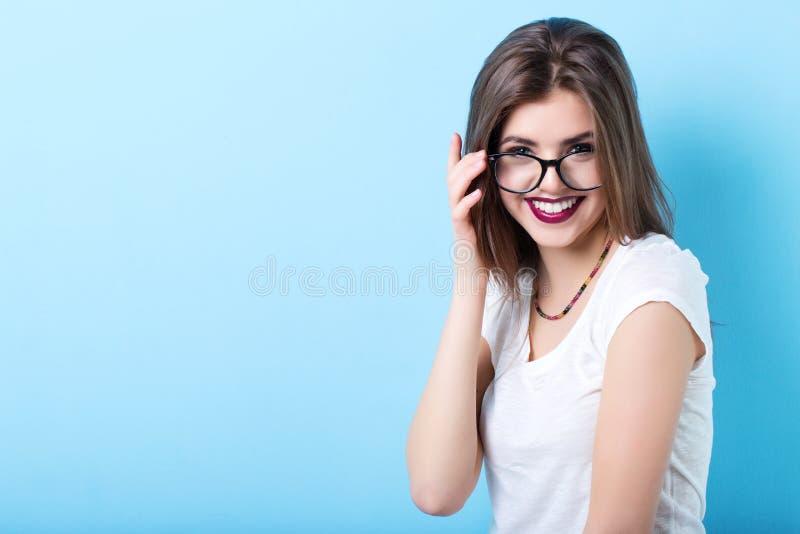 时髦的玻璃的年轻美丽的微笑的女孩 免版税库存照片