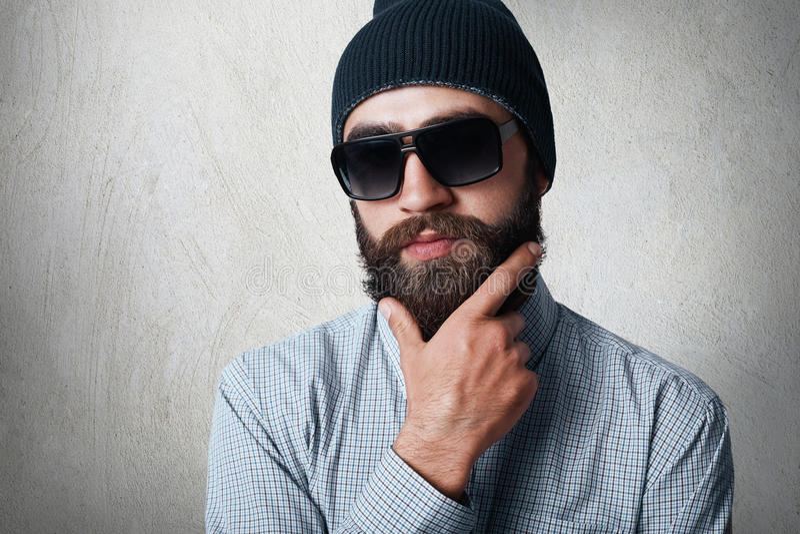 戴时髦的黑盖帽、被检查的衬衣和太阳镜的英俊的有胡子的人特写镜头画象握他的在厚实的胡子的手 免版税库存图片