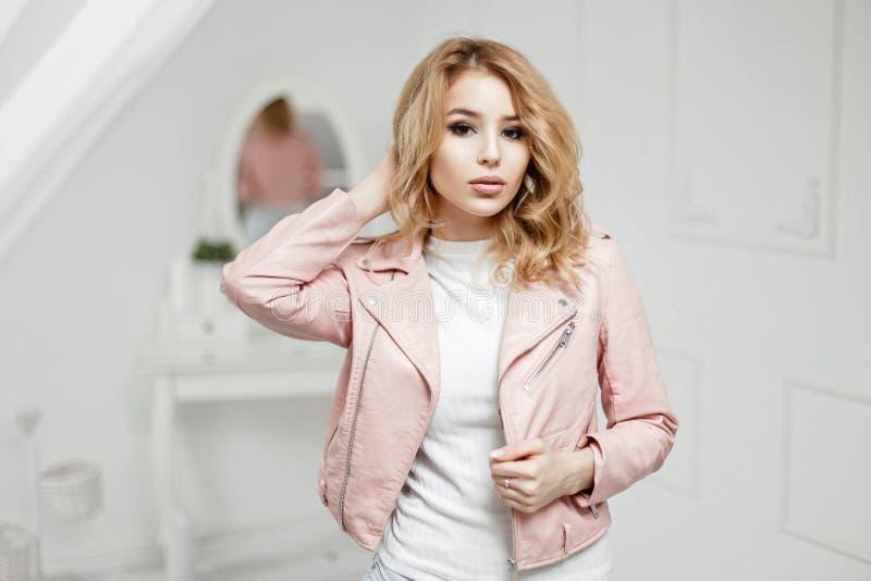 时髦皮夹克摆在的美丽的年轻白肤金发的女孩 免版税库存照片