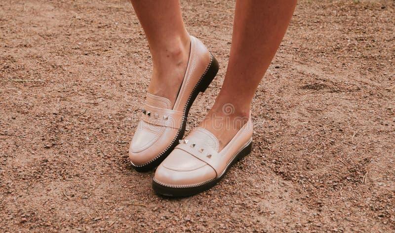 时髦米黄女性游手好闲者 穿上鞋子妇女的 库存图片