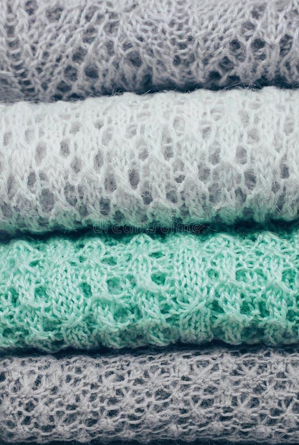 时髦编织了在堆折叠的淡色色的毛线衣 冬天和春季针织品衣物 关闭,复制空间 免版税图库摄影