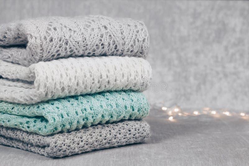 时髦编织了在柔软光滑的织品背景的堆折叠的淡色色的毛线衣 冬天和春季针织品衣物 库存图片