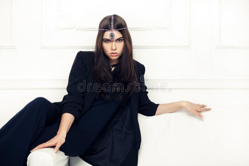 时髦美丽的深色的妇女样式画象一个沙发的与 免版税库存图片