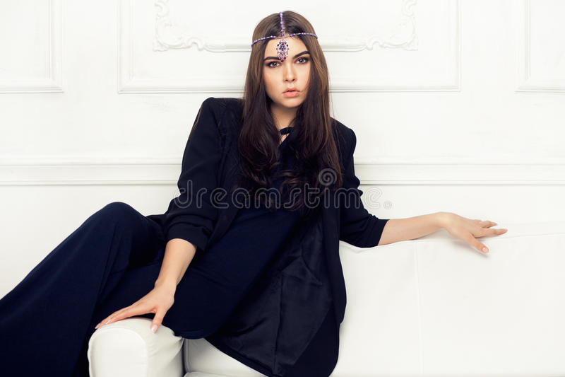 时髦美丽的深色的妇女样式画象沙发的 免版税图库摄影