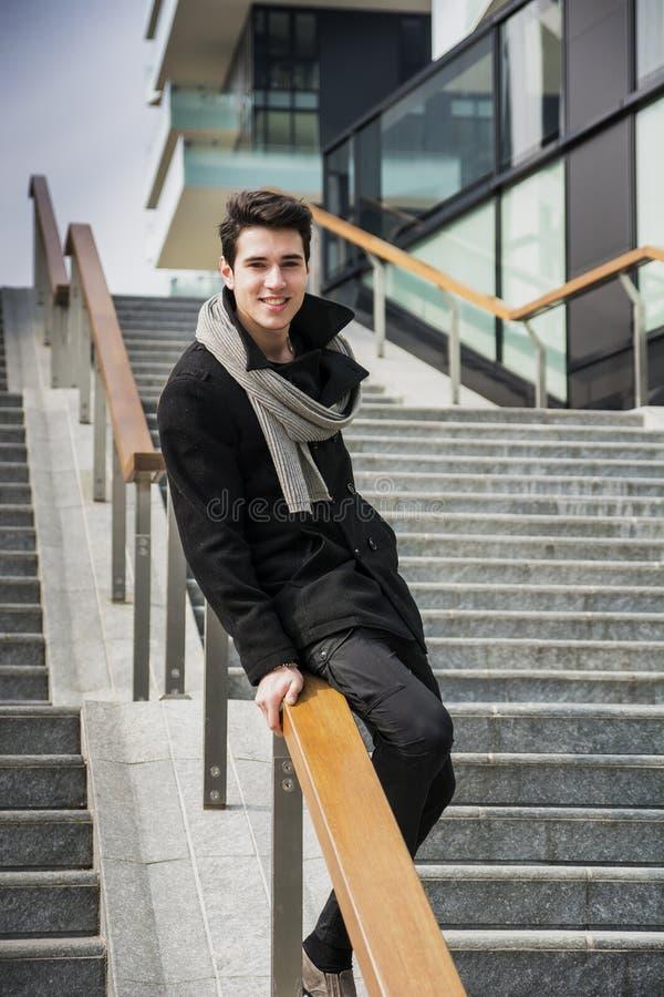 时髦英俊的年轻人以站立在一个长的楼梯的冬天时尚 库存照片