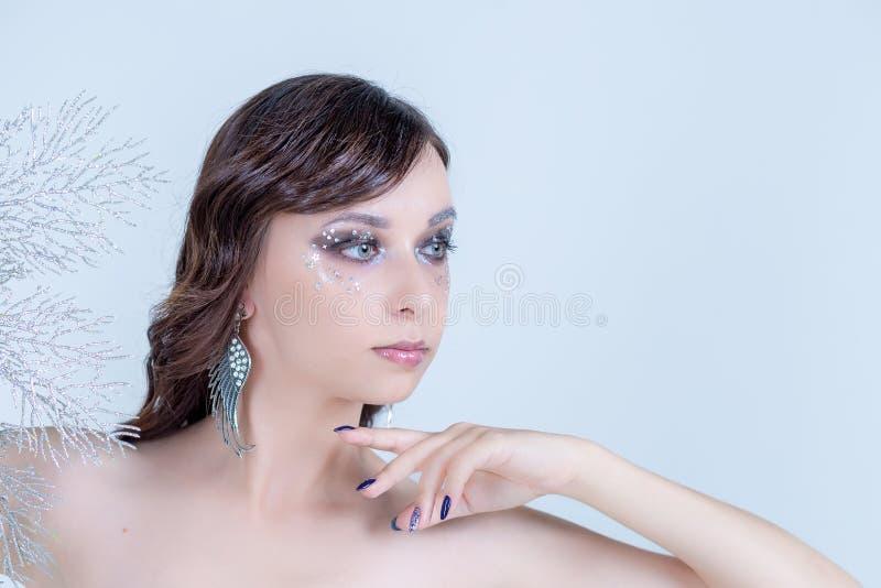 时髦蓝色构成 美丽的少妇用在她的盖一张眼睛和嘴的面孔的手 理想的皮肤 指甲艺术和 库存照片