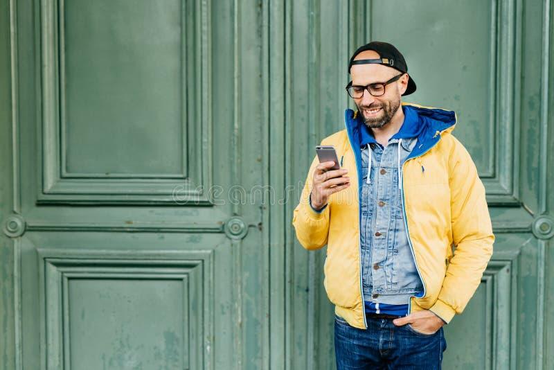 时髦行家画象的腰部有胡子的在握在口袋的便衣穿戴了手看通过在他的网en的新闻 图库摄影