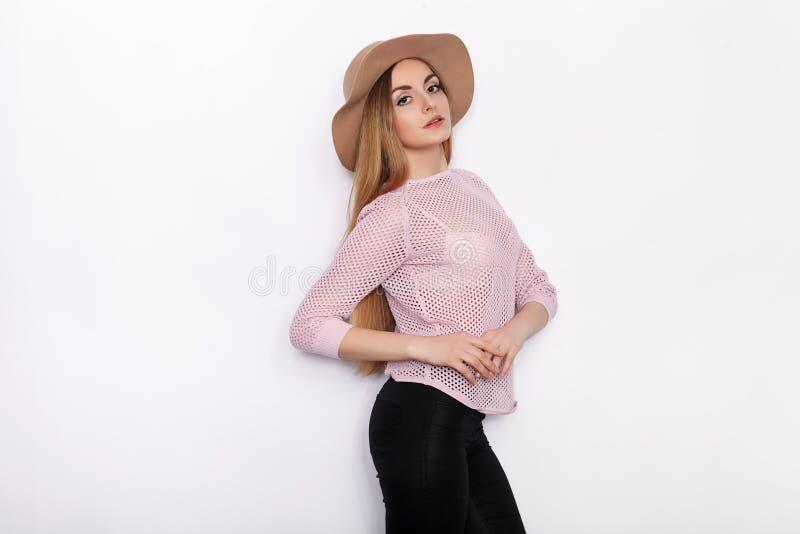 时髦衣物实践的模型姿势的逗人喜爱和时髦的美丽的年轻白肤金发的妇女和看与微笑,当站立时 库存照片