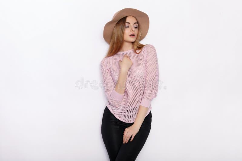 时髦衣物实践的模型姿势的逗人喜爱和时髦的美丽的年轻白肤金发的妇女和看与微笑,当站立时 库存图片