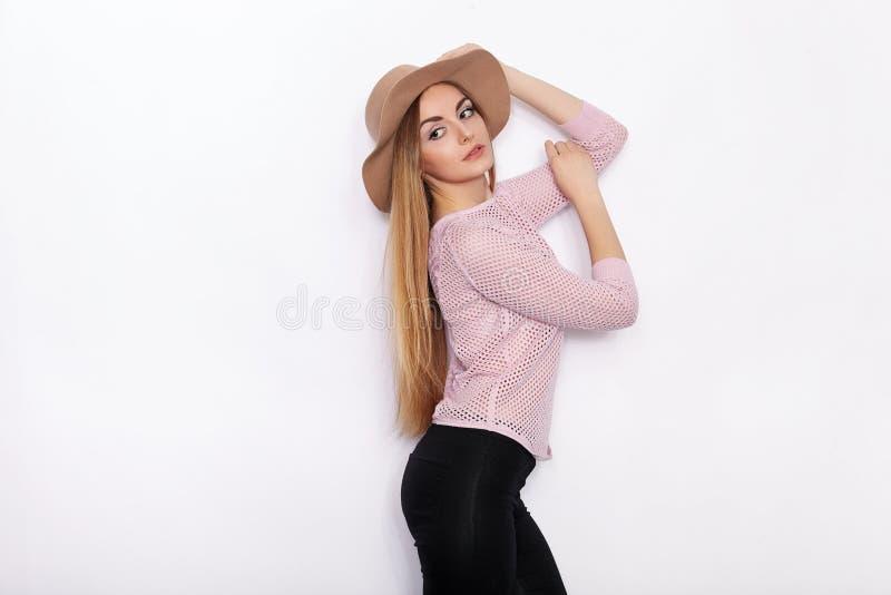 时髦衣物实践的模型姿势的逗人喜爱和时髦的美丽的年轻白肤金发的妇女和看与微笑,当站立时 免版税库存照片