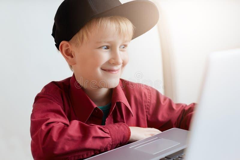 时髦衣裳的一个愉快的小男孩放松在午餐期间在现代咖啡馆,坐在开放膝上型计算机前面使expres惊奇的 免版税库存图片