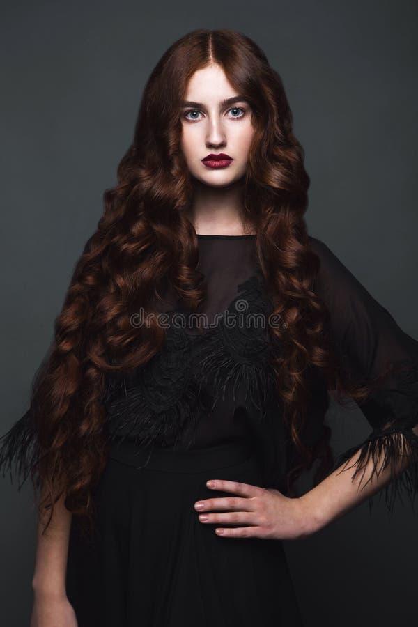 时髦衣裳的美丽的女孩有经典晚上构成和卷毛发型艺术的 秀丽面孔,身体 免版税库存图片