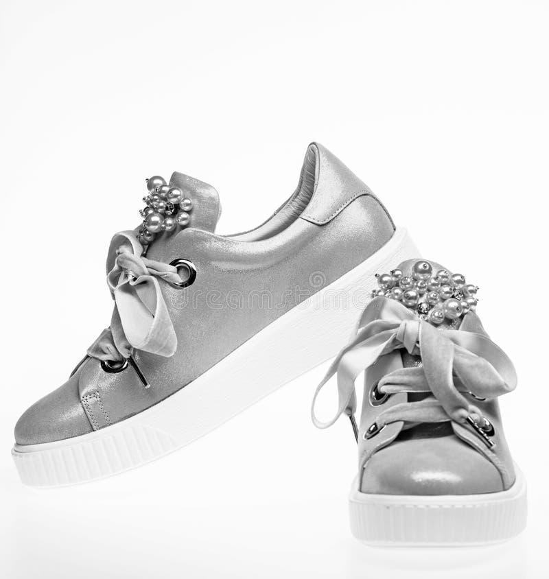 时髦运动鞋概念 用珍珠和妇女的鞋类装饰的女孩成串珠状 对淡粉红的女性运动鞋与 免版税库存照片