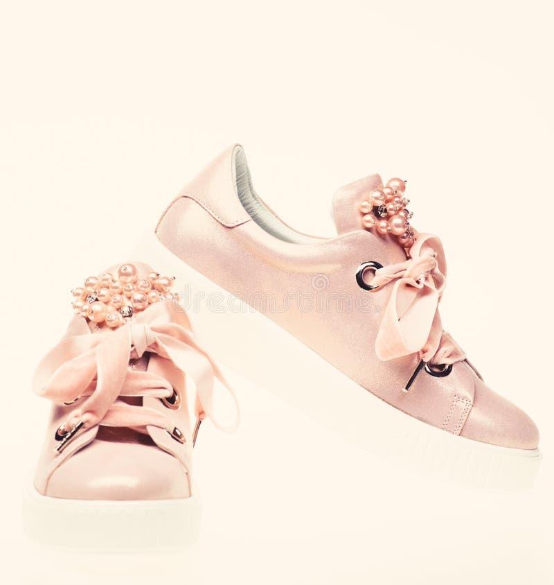 时髦运动鞋概念 用珍珠和妇女的鞋类装饰的女孩成串珠状 对淡粉红的女性运动鞋与 库存图片