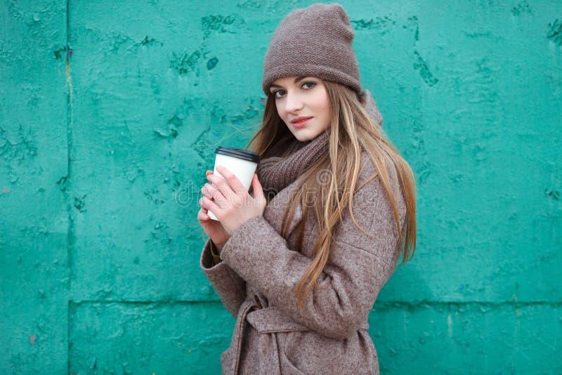 时髦都市的时髦的白肤金发的妇女穿破摆在冷气候反对难看的东西金属绿色被绘的背景 免版税库存图片
