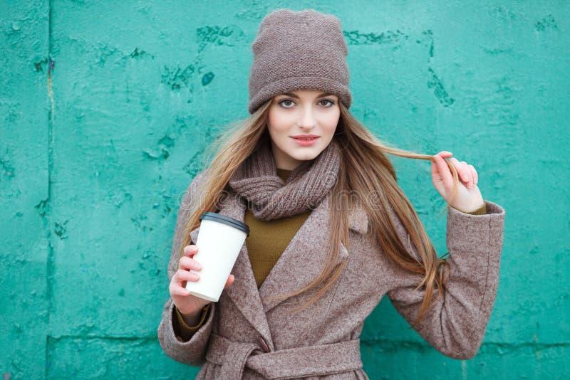 时髦都市的时髦的白肤金发的妇女穿破摆在冷气候反对难看的东西金属绿色被绘的背景 库存照片
