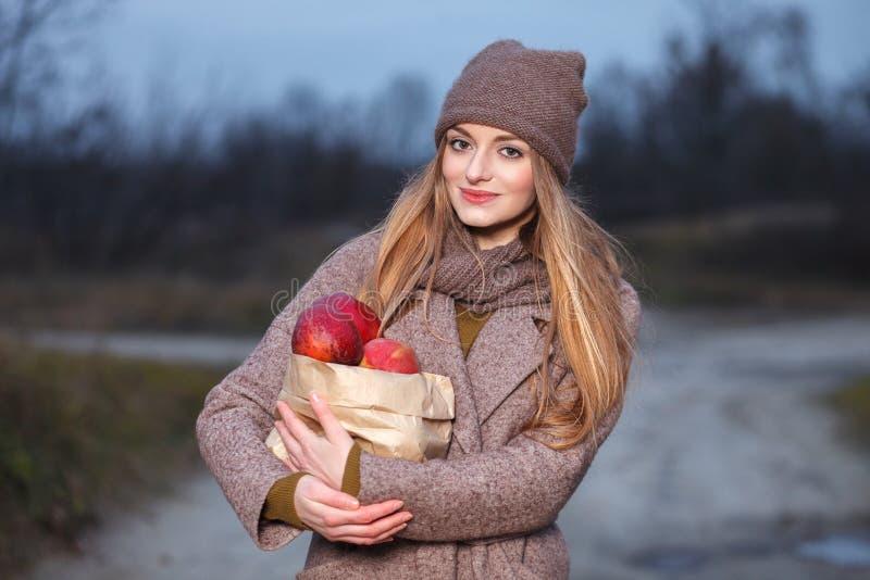 时髦都市的时髦的白肤金发的妇女穿破摆在冷气候有红色苹果包裹的森林公园胡同  秋天心情概念 库存图片