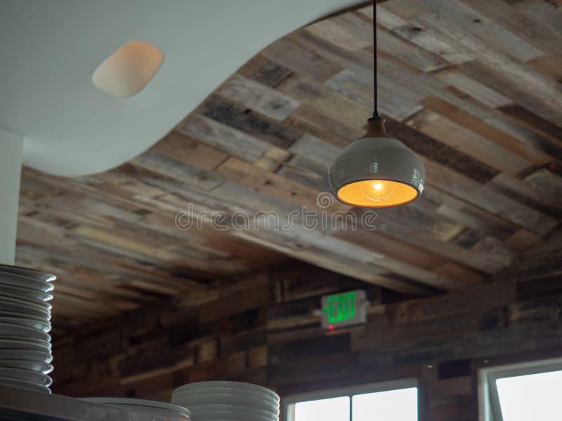 时髦餐馆木屋顶有垂悬的光的和堆陶瓷板材 免版税库存照片
