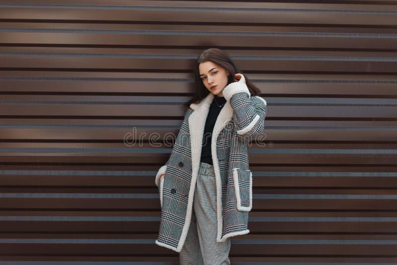 时髦黑T恤杉的可爱的俏丽的年轻女人在灰色时髦的裤子姿势的葡萄酒方格的外套在金属墙壁附近 库存图片