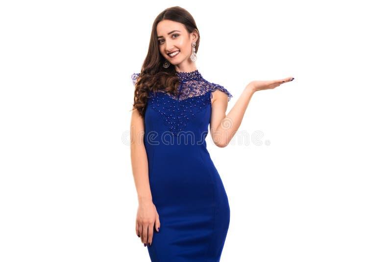 时髦,好,逗人喜爱,白种人妇女画象有发型的在手中举行在空的地方的蓝色礼服 免版税库存图片