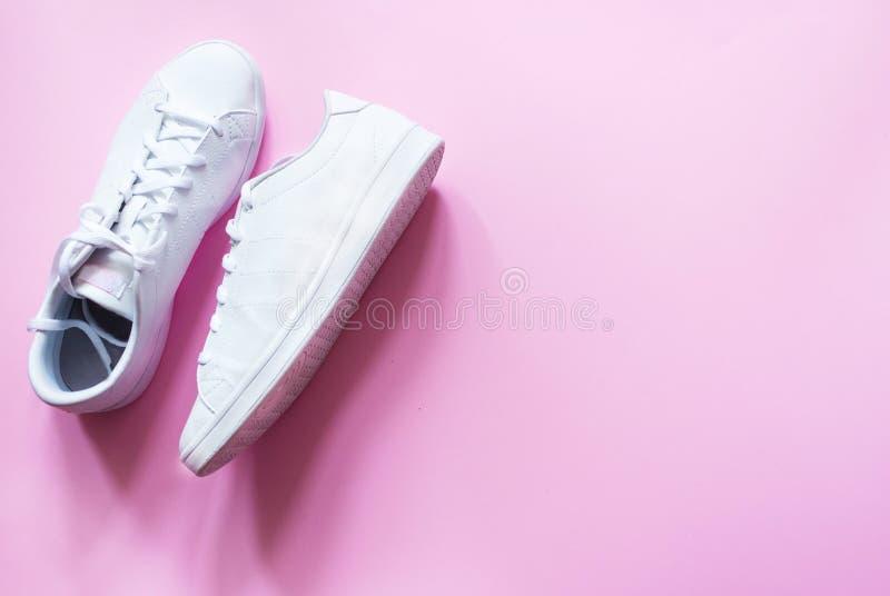 时髦,时髦,行家对在桃红色背景的白色运动鞋 库存图片