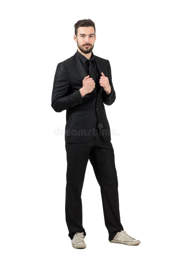 时髦年轻有胡子的商人佩带的白色运动鞋和黑衣服 免版税库存图片